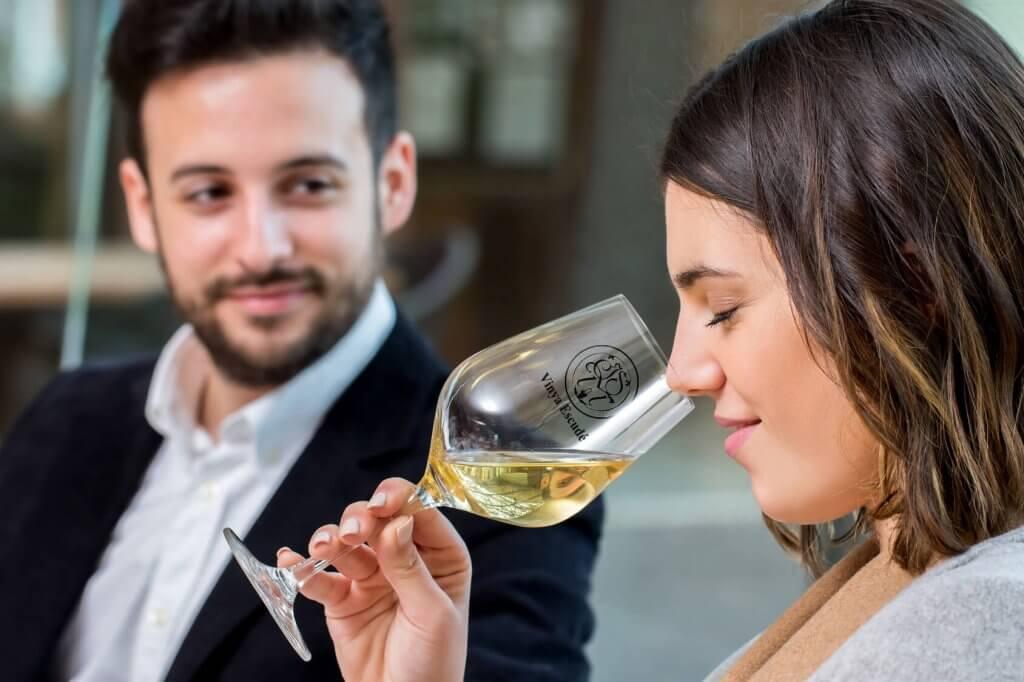 Parella bebent una copa de vi blanc Mil Paraules Vinya Escudé